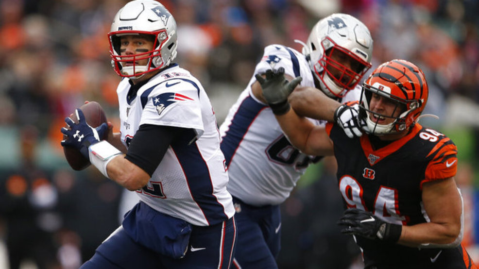 New England Patriots quarterback Tom Brady (12) looks to pass under pressure from Cincinnati Bengals defensive end Sam Hubbard (94) in the second half of an NFL football game, Sunday, Dec. 15, 2019, in Cincinnati. (AP Photo/Gary Landers)